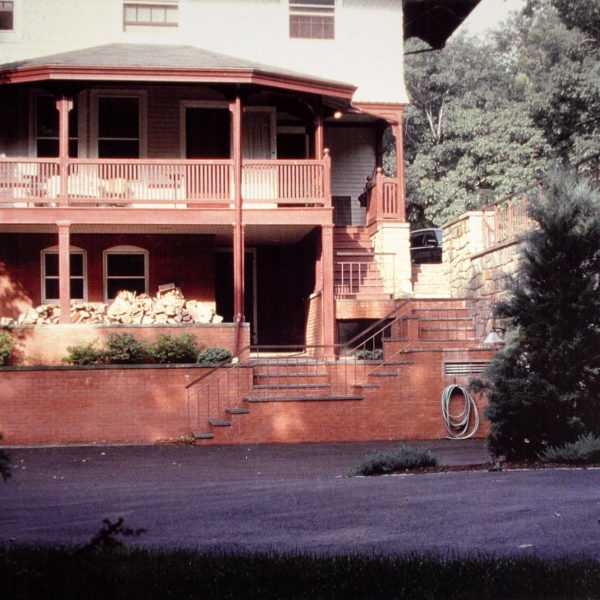 View of rear courtyard, rear entry steps and underground garage wall